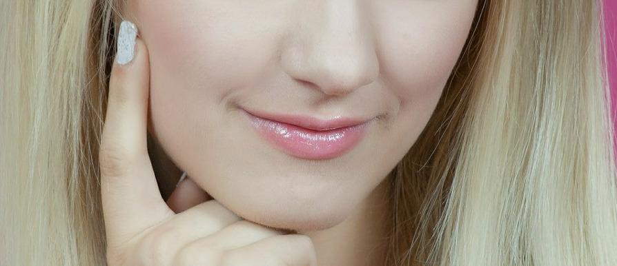девушка прикасается пальцем к гладкой коже своего лица