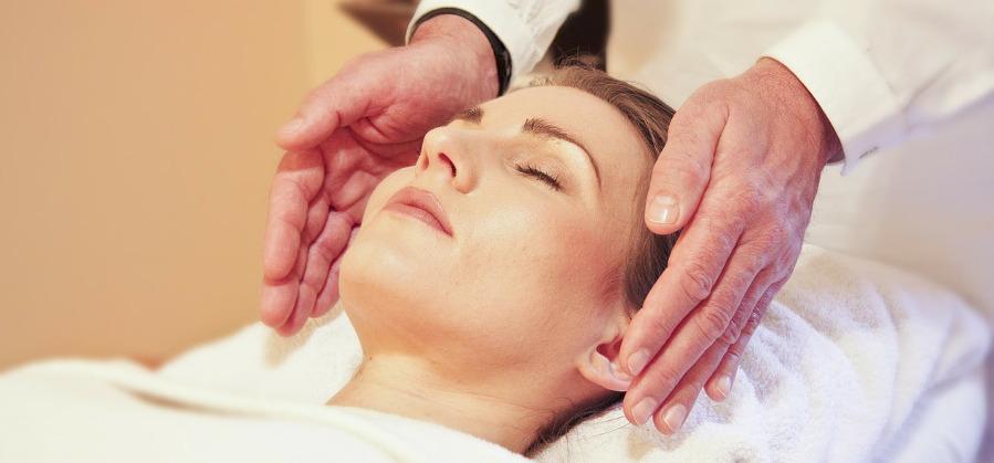 руки косметолога возле лица расслабившейся клиентки