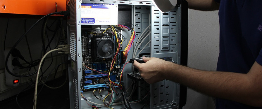 мужские руки разбирают системный блок компьютера