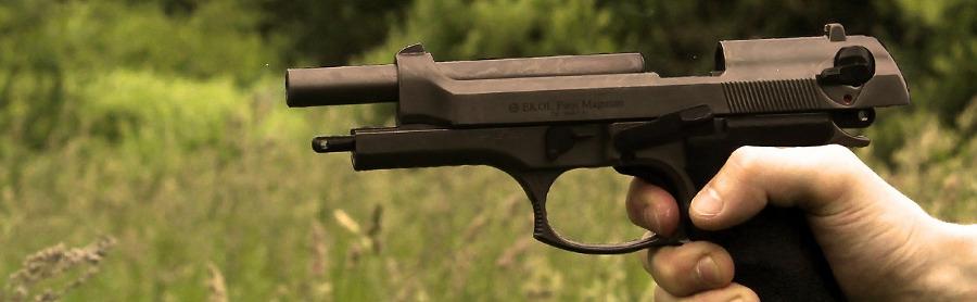 рука с пистолетом на фоне зеленой травы