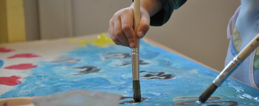 рука ребёнка рисует кисточкой