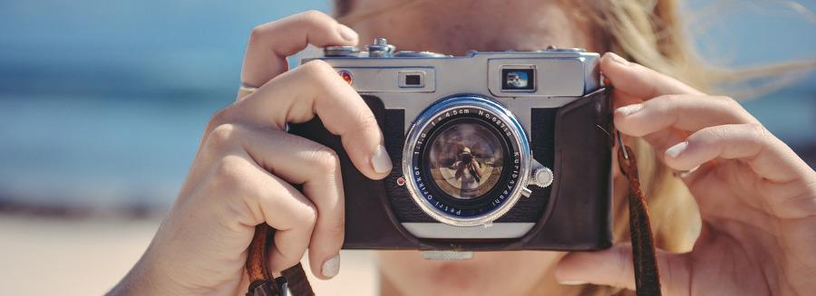 женские руки держат фотокамеру