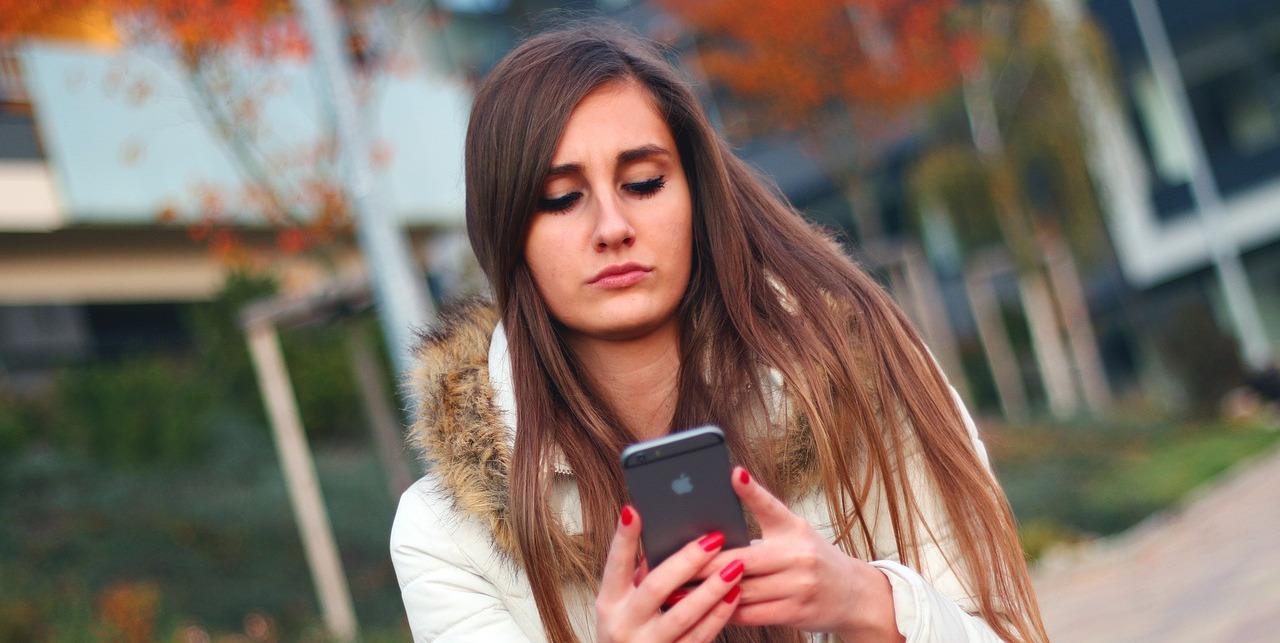 девушка с тревогой смотрит на смартфон