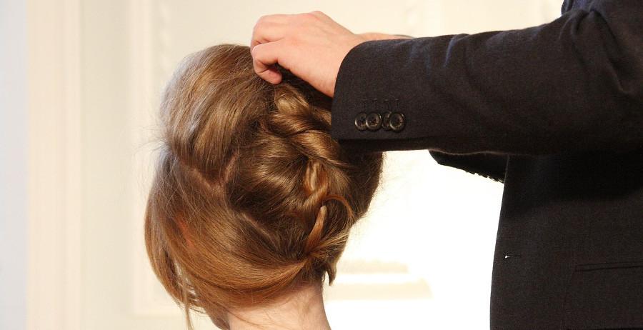 мужские руки поправляют сложную причёску женщины